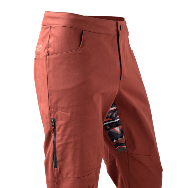 detail of stretch panel Rock pants in rust red for climbing with stretch panel in native red and zip pocket above knee